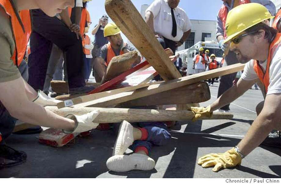 "Rescuers pull away debris as they prepare a cribbing technique used to free a trapped ""victim"". SFFD's Neighborhood Emergency Response Team (NERT) disaster and anti-terrorism drill at Marina Middle School in San Francisco on 6/26/04. PAUL CHINN/The Chronicle Photo: PAUL CHINN"