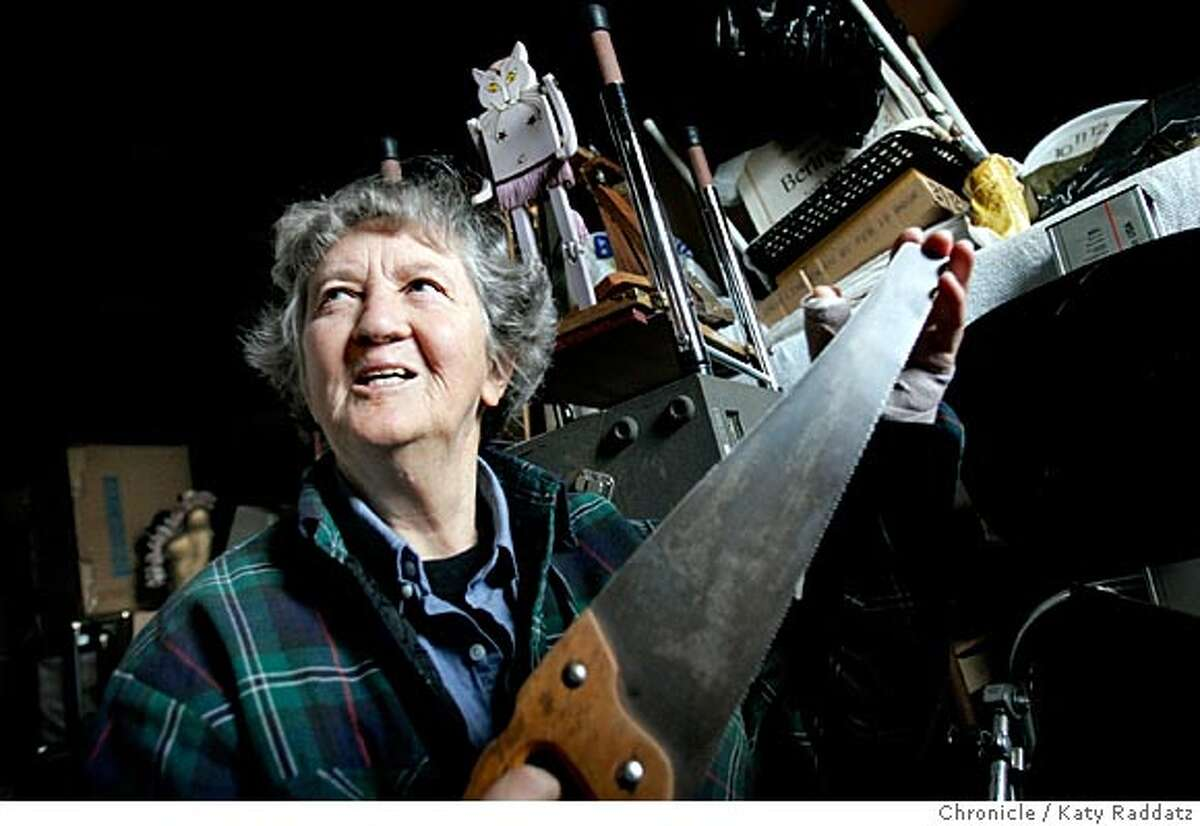 SHOWN: Jackie Jones shows a friend her saw, which is one of the instruments she plays. Behind Jackie stands her famous dancing cat. This photo was made at Jackie's home in San Francisco. This is a profile of Jackie Jones, 78, who has played music at the Alemany Farmers Market for many years. She is a vivid character and has many fans. Jackie recently had surgery on her thumb, and has been unable to make her weekly musical appearance, wherein she plays many instruments, including the saw. When she plays she is accompanied by her self-made dancing cat. Photo taken on 1/17/05, in SAN FRANCISCO, CA. By Katy Raddatz / The San Francisco Chronicle
