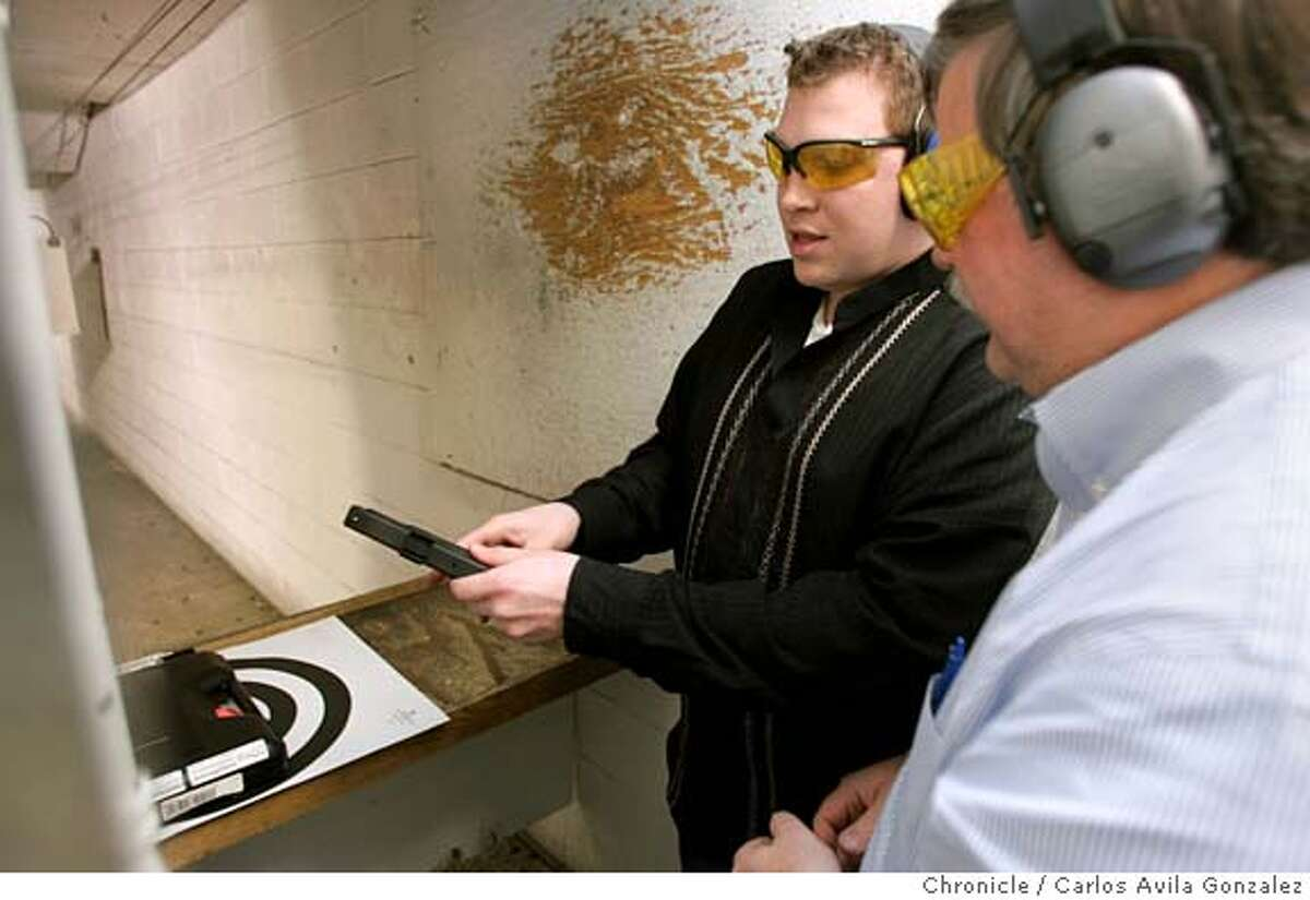 PISTOLS03_038_CAG.JPG Aaron Thomas, left, of San Francisco, and Richard Newell, right, of Walnut Creek, discuss a gun while target shooting at Jackson Arms Shooting Range in South San Francisco, Ca., on Tuesday, February 1, 2005. Against all stereotypes, this organization of gay men and lesbians advocates gun rights in San Francisco. They call themselves the Pink Pistols and they�ve found a new battle to fight now that the San Francisco supervisors want to make the city the second in the nation to ban the ownership of handguns. Photo by Carlos Avila Gonzalez / The San Francisco Chronicle Photo taken on 2/1/05 in South San Francisco, CA. MANDATORY CREDIT FOR PHOTOG AND SAN FRANCISCO CHRONICLE/ -MAGS OUT