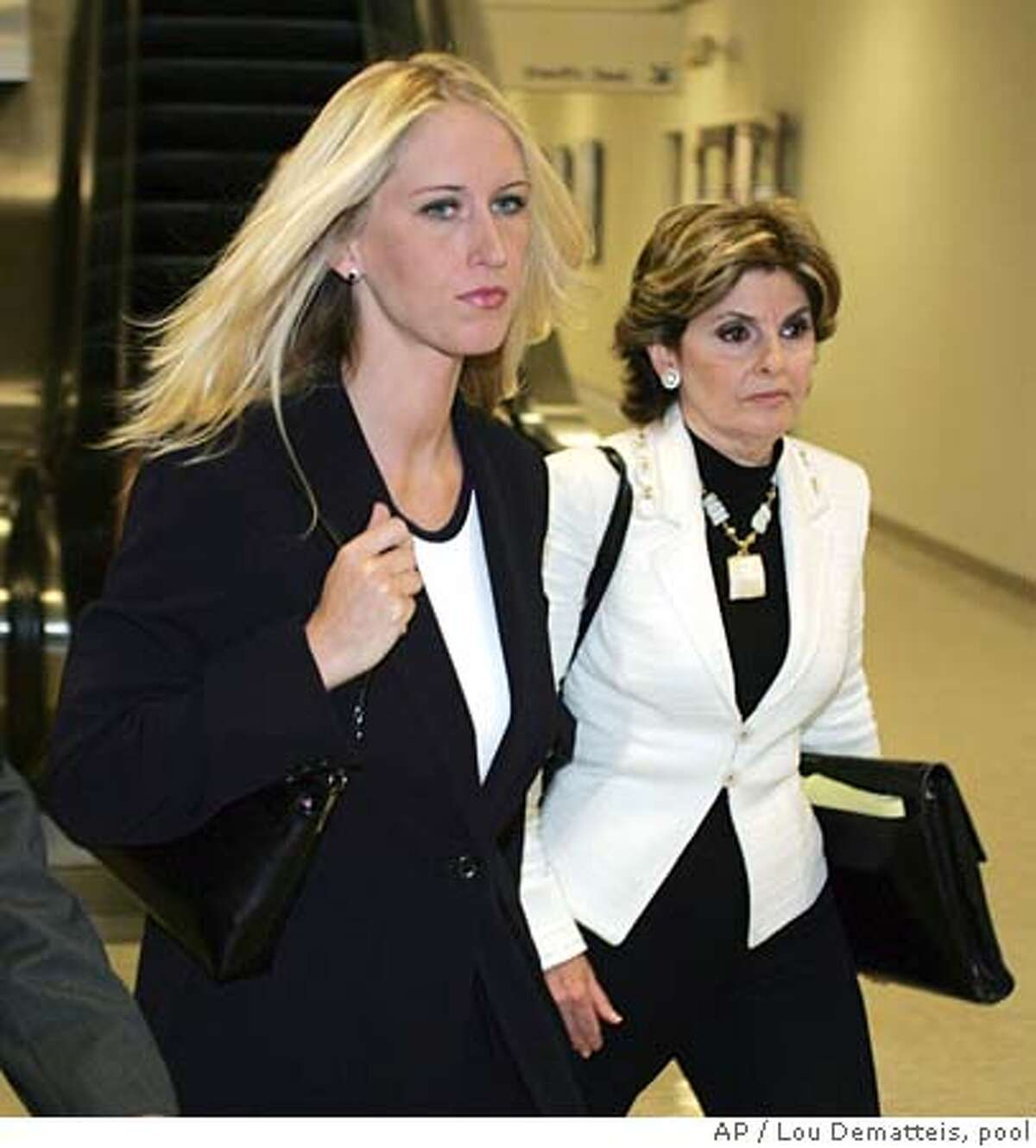 With her attorney Gloria Allred at right, Amber Frey leaves the courthouse after her second day of testimony during the Scott Peterson double murder trial in Redwood City, California, Aug. 11, 2004. (AP Photo/Lou Dematteis, pool) POOL PHOTO