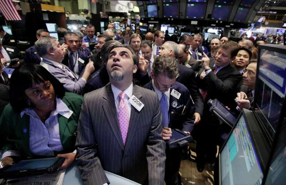 Traders crowd the on the floor of the post of specialist Jason Blatt, center, for the IPO of Guidewire Software, on the floor of the New York Stock Exchange Wednesday, Jan. 25, 2012. Guidewire President and CEO Marcus Ryu, second from right, watches the action. (AP Photo/Richard Drew) Photo: Richard Drew