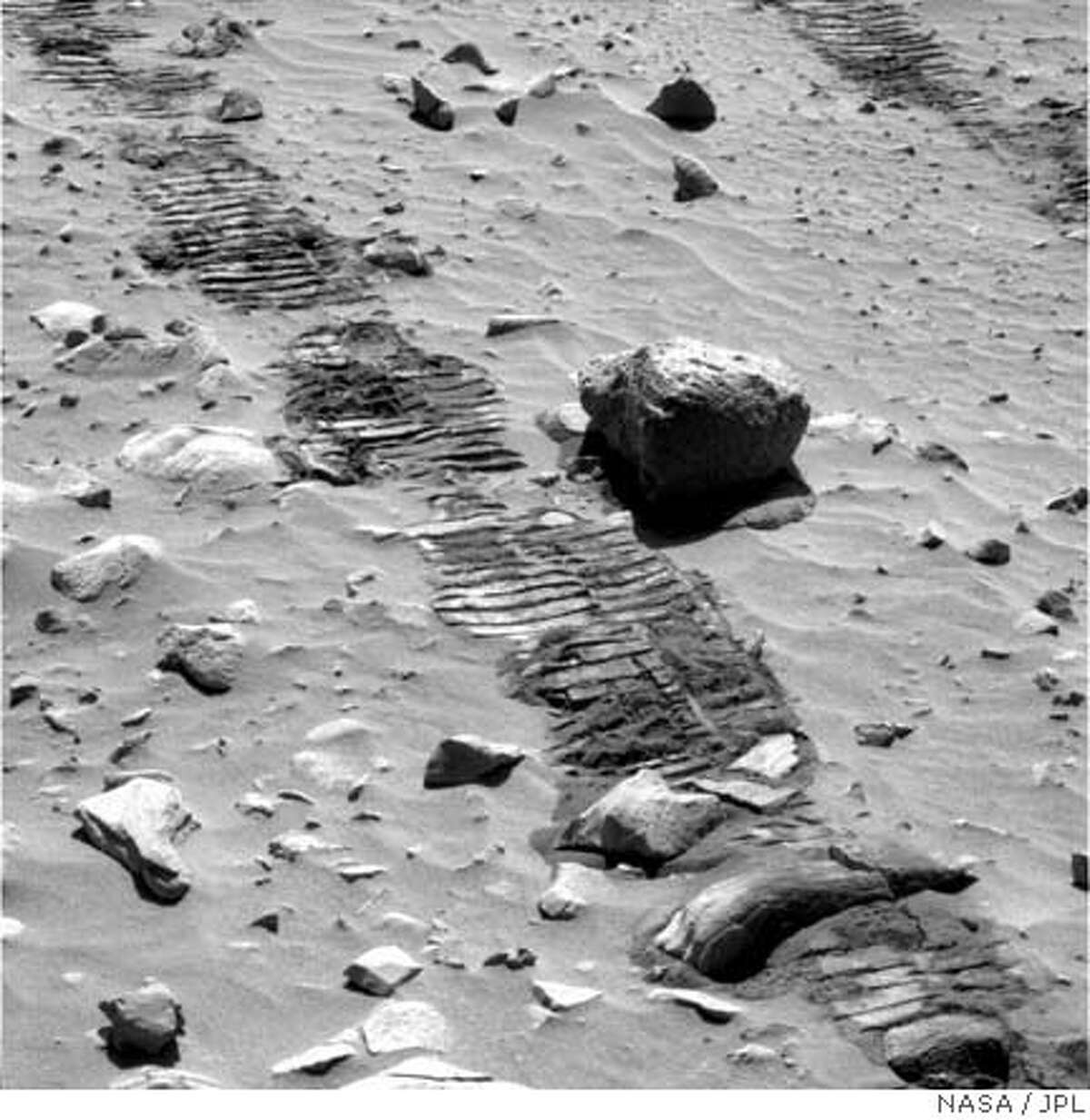 MARS04.JPG Track marks left by the Spirit Rover. Courtesy of Cornell/JPL/NASA Ran on: 08-09-2004 Looking for all the world like the track marks of a dune buggy on a California beach, these tracks of the Spirit rover on Mars reveal every parallel indentation of the wheels metal treads as they roll over a small rock and the finely drifted sand forming soft ripples from the Martian winds. Ran on: 08-09-2004