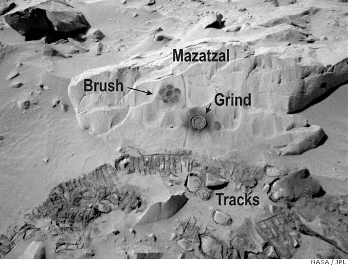 Spirit carries other cameras besides the Pancams, and this image of a 7 1/2-foot-wide rock was taken by the rover's navigation camera, called the Navcam. It was labeled by the imaging team to show where the rover's rock abrasion tool brushed away some of the rock's fine sand-covered surface and then ground beneath the surface like a broad-bitted drill so instruments could determine the rock's structure and chemistry. Photo courtesy of NASA