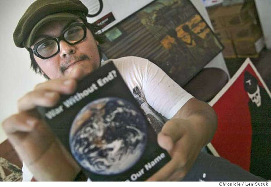 Artist Manny Silva holds a Not in our Name postcard behind him are some of the works for the show in New York. postcard. Artist Manny Silva, will be co-curating an art show in New York on behalf of the antiwar group Not In Our Name and collected art at Mama Buzz Cafe on August 4th from other artists for the show in New York. From artists to anarchists to unionists to anti-war activists, Bay Area residents will be among the prime ringleaders and participants at the GOP convention in New York City at the end of August. In fact, some have been there all summer, walking the boroughs and riding the trains, encouraging locals not to leave town and instead fire a raspberry at President Bush and his supporters. Others will be taking a different tack, like artist Manny Silva, who will be co-curating an art show in New York on behalf of the antiwar group Not In Our Name. On Wednesday, Manny will be at an Oakland space, collecting pieces from other artists destined for the show. He will also have a couple of his pieces in the show there. He will be at Mama's from 10a.m. to 7 p.m. Photo taken on 8/4/04 in Oakland, CA.  Lea Suzuki/ San Francisco Chronicle Photo: Lea Suzuki