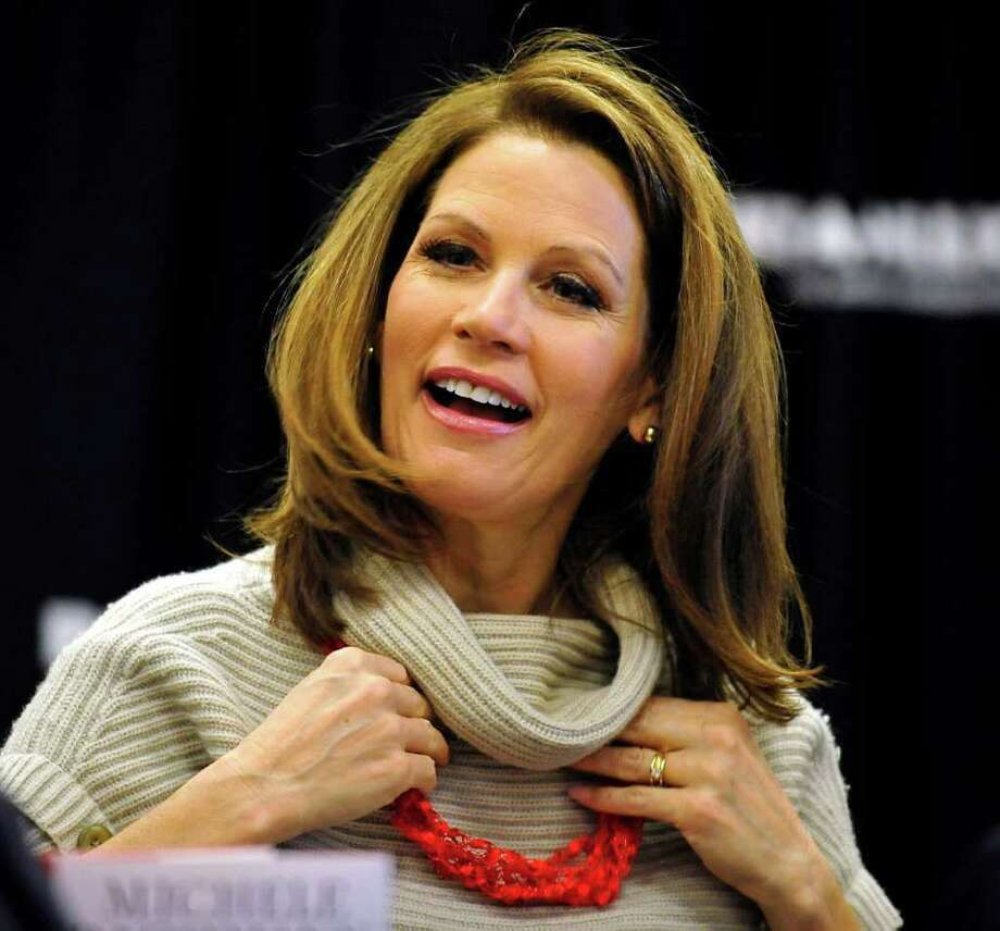 FILE - In this Dec. 3, 2011, file photo Republican presidential candidate Rep. Michele Bachmann, R-Minn., expresses appreciation as she puts on a gift from a supporter during the book-signing event  in Aiken, S.C.  Bachmann told The Associated Press Wednesday, Jan. 25, 2012, that she'll seek a 4th term in Congress following her failed presidential bid. (AP Photo/Rainier Ehrhardt, File) Photo: Rainier Ehrhardt / AP2011