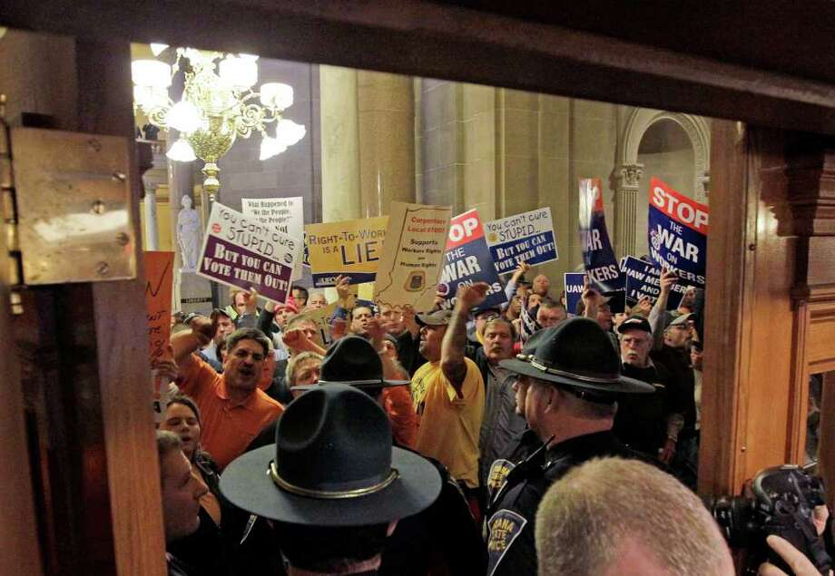 Indiana State Police stand at the entrance of the House of Representatives during a debate on the right-to-work bill at the Statehouse on Wednesday Photo: Darron Cummings / AP