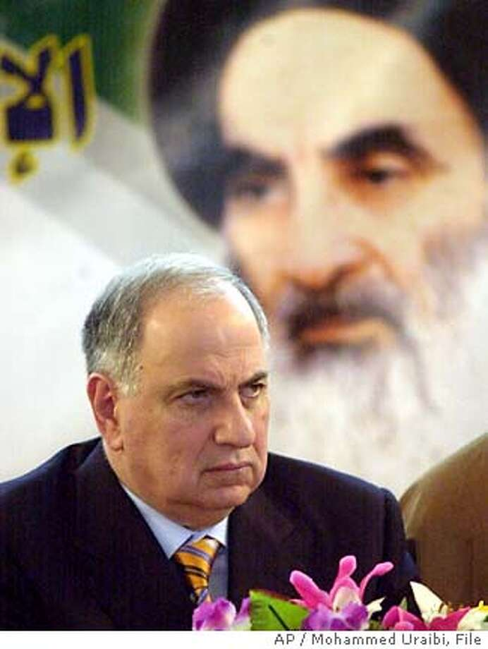 Shiite politician Ahmad Chalabi sits below the poster of Grand Ayatollah Ali al-Sistani during a news conference in Baghdad, Saturday, Jan. 15, 2005. As the majority of Sunni Muslims are expected to boycott the elections, many Shiites, who make 60 percent of Iraq's 26 million people and have been ruled by Sunnis since Iraq was created in 1932, are working hard to win majority seats in the 275-member National Assembly in the Jan. 30, elections (AP Photo/Mohammed Uraibi) Photo: MOHAMMED URAIBI