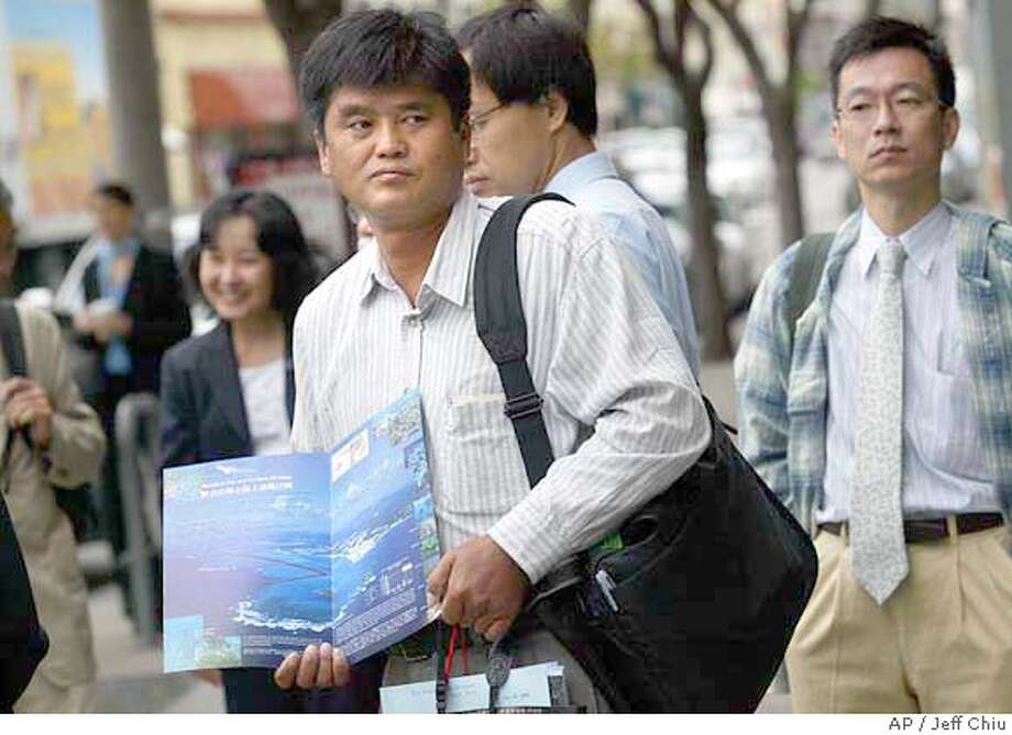 Higashionna Takuma, center, a fisherman and boat captain from Okinawa, Japan, prepares to enter the U.S. District Court for the Northern District of California for the hearing of Okinawa Dugong v. Rumsfeld in San Francisco on Wednesday, Aug. 4, 2004. A dugong is a marine mammal related to the manatee. Higashionna is part of a delegation of Japanese residents contesting a plan by the U.S. military to build an airbase off the coast of Okinawa in a shallow bay that provides dugong feeding grounds. (AP Photo/Jeff Chiu) Photo: JEFF CHIU