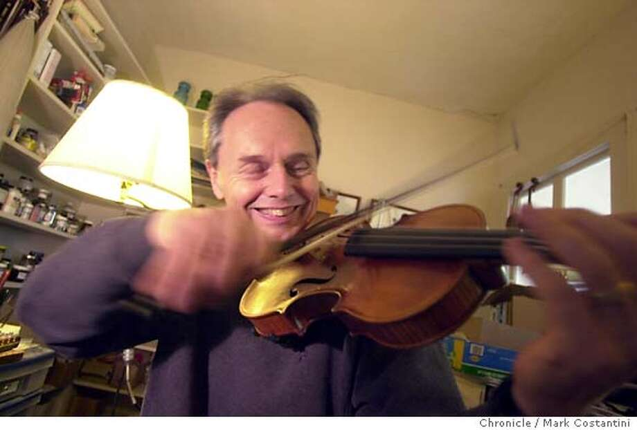Patrick , expert violin maker in his studio. He's having fun playing one he made for Kronos Quartet member. 7/15/04 in BERKELEY. Chronicle Photo by Mark Costantini Photo: MARK COSTANTNI