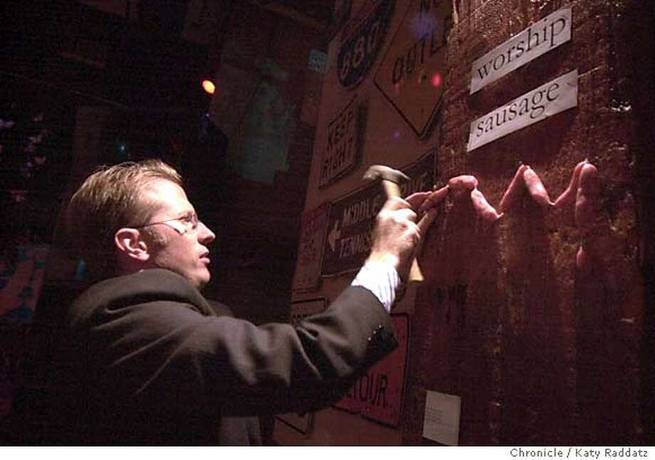 """LITQUAKE30055_rad.jpg SHOWN: Terry Wellman, the curator of the show, hangs Don Novello's art piece titled """"Worship Sausage"""" at a Magnetic poetry event to benefit Litquake. Katy Raddatz / The Chronicle Ran on: 07-31-2004  Curator Terry Wellman hangs &quo;Worship Sausage,&quo; artwork made from Molinari sausages, by actor Don Novello. Photo: Katy Raddatz"""