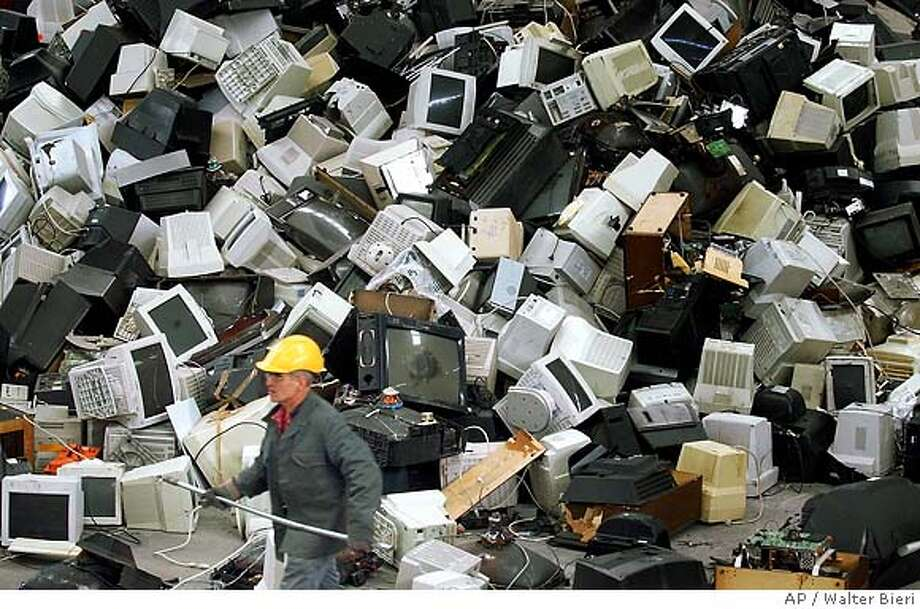 A worker passes piles of computer monitors at one of Europe's most modern recycling plants for electronic devices in Regensdorf, Switzerland, Friday, March 26, 2004. Switzerland recycles 30,000 tons of electronic garbage per year. (AP Photo/ Keystone, Walter Bieri) ** SWITZERLAND OUT ** Photo: WALTER BIERI