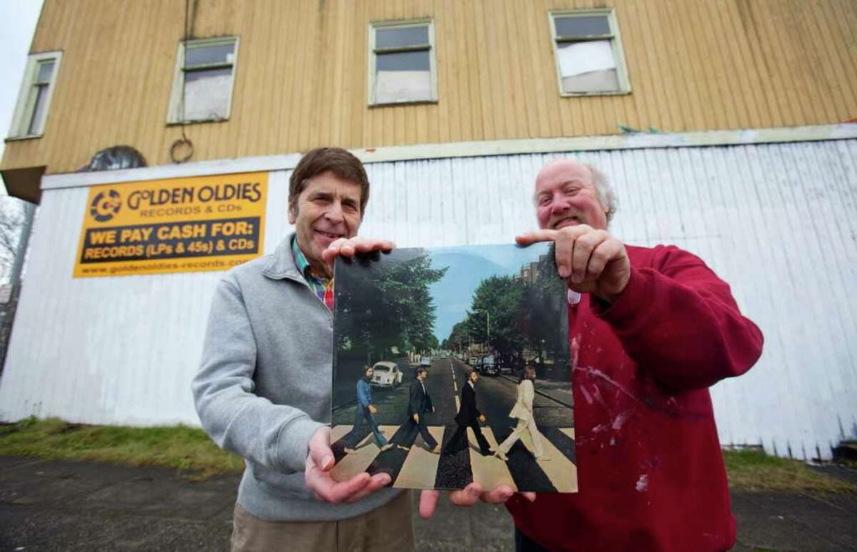 Dean Silverstone, left, owner of Golden Oldies records, and locally reknown mural artist David Heck, hold The Beatles' album Abbey Road in front of the record store on Wednesday, January 25, 2012 in Seattle's Wallingford neighborhood. Over the next few days, Heck will recreate what is one of the most iconic album covers on the side of the building.