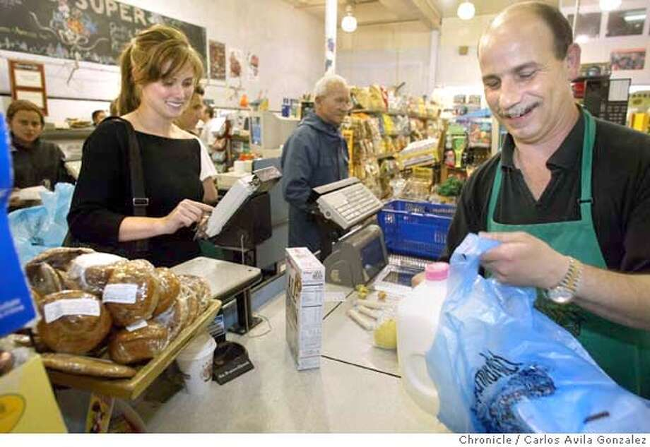 At Marina Super Market on Chestnut Street in San Francisco, Ca, 'Broadway Bob' (this is the name he gave photographer) bags a gallon of milk for Nikki Tankursley, on Wednesday, July 28, 2004. The gallon of milk cost about $5.00. Consumers Union survey finds Bay Area milk shoppers are being gouged. They find that large supermarket chains are charging more per gallon than local mom & pop markets. For example in Berkeley, Andronico's Market charged $5.05 for a gallon of Clover brand whole milk and $4.89 for a gallon of Berkeley farms whole milk, while Mi Ranchito charged $3.29 for a gallon of Berekely farms.  Photo taken on 07/28/04n San Francisco, Ca. Photo By Carlos Avila Gonzalez / The San Francisco Chronicle Photo: Carlos Avila Gonzalez