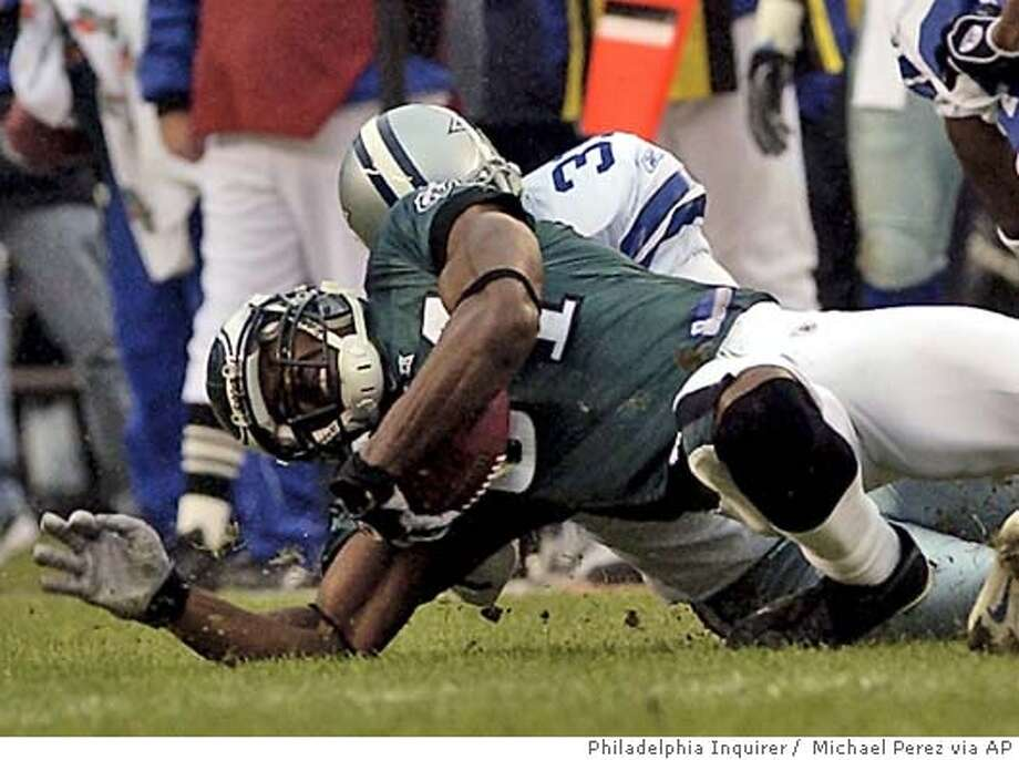 Philadelphia Eagles Terrell Owens, bottom, is tackled by Dallas Cowboys Roy Williams in the third quarter, Sunday, Dec. 19, 2004, in Philadelphia. Owens was injured on the play and will miss the rest of the regular season and possibly the playoffs and Super Bowl with torn ligaments in his right ankle. The Eagles won 12-7. (AP Photo/Philadelphia Inquirer, Michael Perez) Ran on: 12-21-2004  Terrell Owens will be out for the rest of the regular season and at least most of the playoffs. Ran on: 12-21-2004  Terrell Owens will be out for the rest of the regular season and at least most of the playoffs. TV OUT, MAGS OUT, Photo: MICHAEL PEREZ