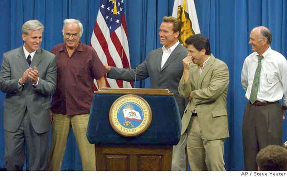 Gov. Arnold Schwarzenegger, center, jokes with legislative leaders, left to right, Assemblyman Kevin McCarthy, R-Bakersfield, Sen. John Burton, D-San Francisco, Assembly Speaker Fabian Nunez, D-Los Angeles, and Sen. Dick Ackerman, R-Fullerton, during a news conference to announce an agreement on an estimated $103 billion budget at the Capitol in Sacramento, Calif., on Monday, July 6, 2004.(AP Photo/Steve Yeater) Photo: STEVE YEATER