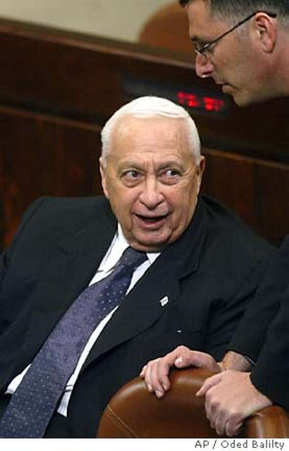Israeli Prime Minister Ariel Sharon smiles prior to a session in the Knesset, Israel's parliament, for the budget vote, in Jerusalem Wednesday Jan. 12, 2005. Sharon's new government survived its first test Wednesday, with the parliament voting in favor 64-53 of his 2005 state budget. Rebels in his Likud Party supported the spending plan in the first of three required votes, but threatened to oppose the plan in the future _ threatening to topple him and delaying his plan to withdraw from the Gaza Strip. (AP Photo/ Oded Balilty) Photo: ODED BALILTY