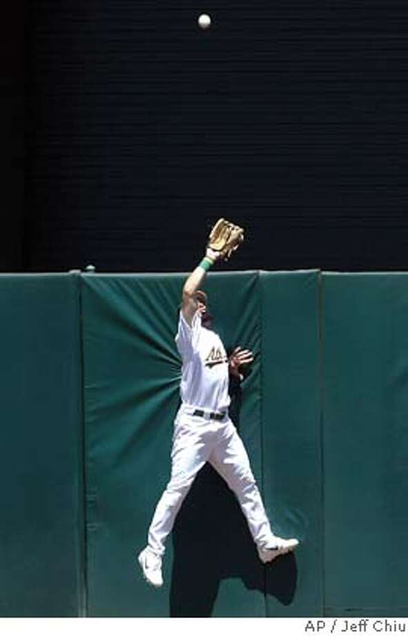 Oakland Athletics center fielder Mark Kotsay leaps to rob Texas Rangers' Mark Teixeira of a possible three-run home run in the third inning in Oakland, Calif., Sunday, July 25, 2004. The Athletics won, 9-2. (AP Photo/Jeff Chiu) Photo: JEFF CHIU