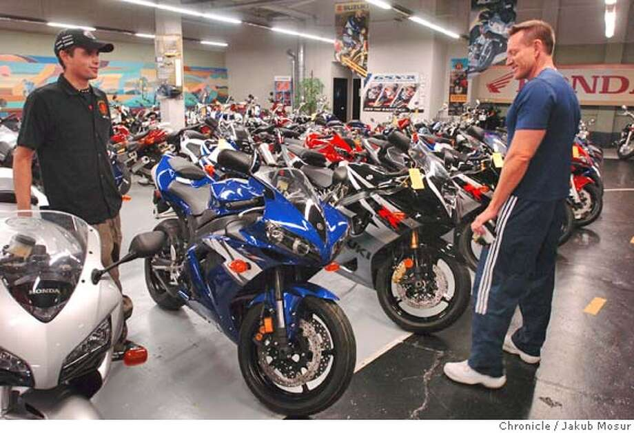 Britt Hahn, 44, left, of San Francisco looks at a Yamaha R1 before purchasing it for Corporal Korey Calloway, who had returned from Iraq after receiving two Purple Heart Medals and to have his motorcycle stolen, at the Golden Gate Cycles on Saturday, 7/24/04 in San Francisco. Daniel Reiss, an employee of Golden Gate Cycles, helps Hahn choose the right motorcycle. JAKUB MOSUR / The Chronicle Photo: JAKUB MOSUR