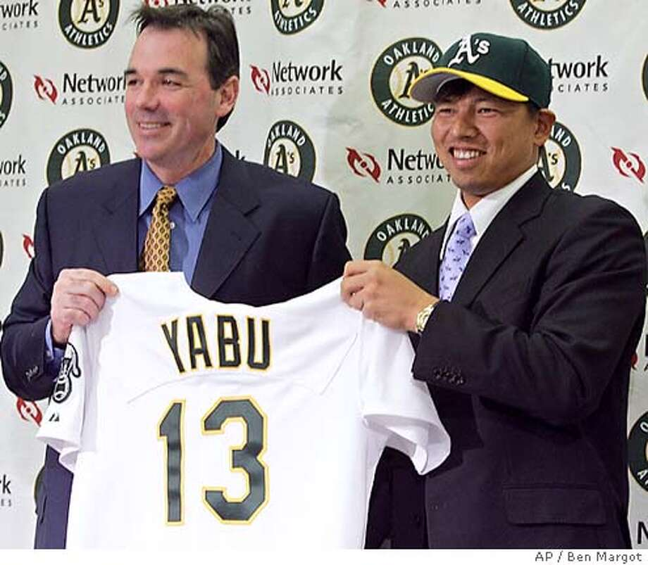 Oakland Athletics' general manager Billy Beane, left, holds up the jersey of his newest player, Japanese pitcher Keiichi Yabu during a media conference Thursday, Jan. 13, 2005, in Oakland, Calif. (AP Photo/Ben Margot) Photo: BEN MARGOT