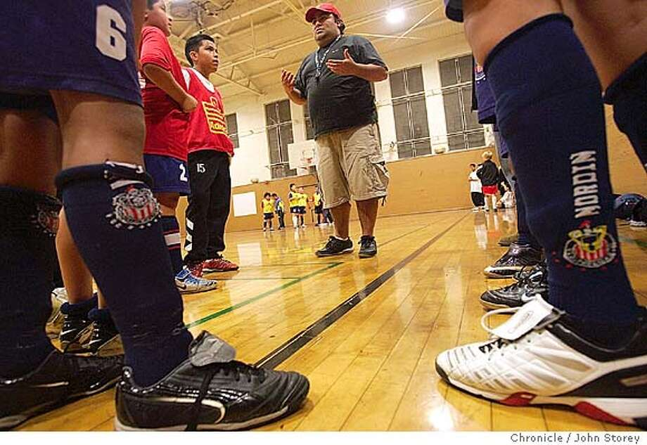"""Coach William Martinez talks with his players during practice. The gym at Horace Mann Middle School, long a haven for Mission District kids practicing soccer in the evenings, is closing, due to budget cuts at the Recreation and Park Department. The assistant recreation director who has been staffing the gym in the evenings has been reassigned.  Kids aged 6 to 13 play soccer from 6-8 p.m., adults (women playing in the Golden Gate Women's Recreational Soccer League) take over the gym from 8-9 p.m., Monday through Thursday.  One of the youth teams is """"JC Chivas USA,"""" an under-12 team that plays in the Police Activity League in the city. They will be practicing Thursday night. They are coached by a guy who grew up playing soccer in the same gym.  1/6/05 San Francisco, CA John Storey/The Chronicle Photo: John Storey"""