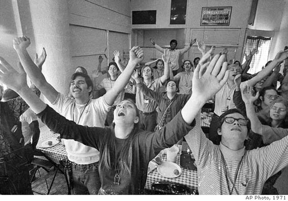 "Youthful members of an informal Christian group called "" "" sing before sitting down for lunch at their headquarters building in the skid row section of Los Angeles on Feb. 2, 1971. The group - one segment of southern California's fast growing ""Jesus Movement"" - trains young people to walk the streets and beaches seeking to convert other young street people to Christianity. (AP Photo)"