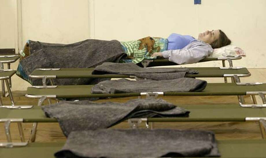 A woman rests at an evacuation center at Corona High School in Riverside County on Friday. More than 2,000 homes were evacuated from the flood path of a dam after water began seeping from an earthen barrier, prompting authorities to release millions of gallons of water to relieve pressure. Associated Press photo by Nick Ut
