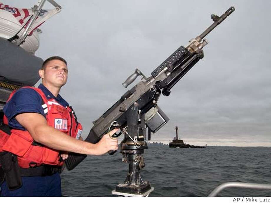 Coast Guard Petty Officer Third Class Albert Herrington of Mason, TX, patrols Boston Harbor, Saturday, July 24, 2004, in preperation for the Democratic National Convention. (AP Photo/USCG, PO Mike Lutz) US COAST GUARD HANDOUT Ran on: 07-25-2004  Coast Guard officer Albert Herrington, with his hands on a machine gun, patrols Boston Harbor. Photo: MIKE LUTZ