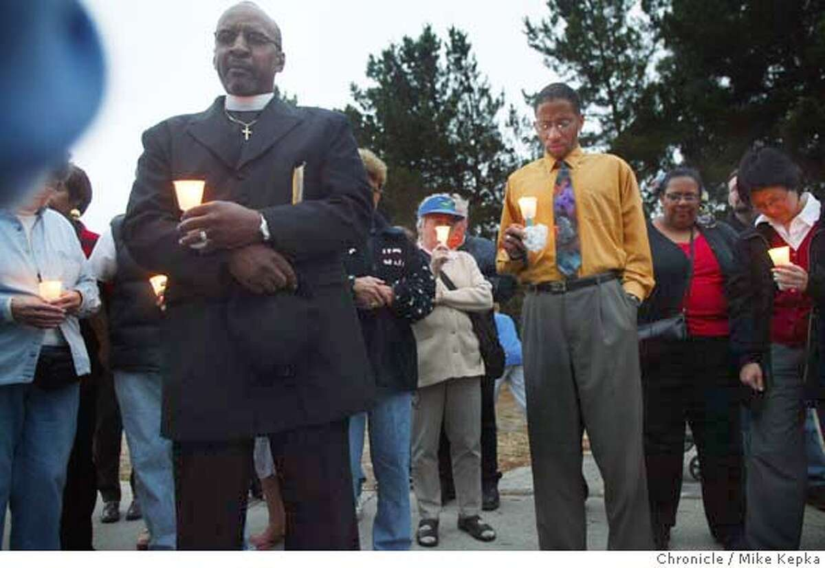 The Reverand Willie Darden leads a closing prayer with a group of Richmond community members who gathered Thursday night for praye a candlelight protest of a proposal where the West Contra Costa Unified School District would combine Gompers and North Campus at an old elementary school site less that a mile from Contra Costa College. MIKE KEPKA/The Chronicle