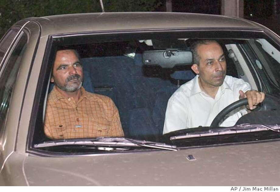 The diplomat, identified as Mohammed Mamdouh Helmi Qutb, right, alongside Alsayeid Mohammed Alsayeid Algarabawi, left, an Egyptian truck driver held hostage for two weeks, arrives at the Egyptian Embassy in Baghdad, Iraq, after Alsayeid's release Monday, July 19, 2004. Mohammed Mamdouh Helmi Qutb was shown seated in front of six masked kidnappers in a video broadcast Friday July 23, 2004 on the Al-Jazeera television station. The group, which called itself the Lions of Allah Brigade, said it had abducted him because the Egyptian government had said it was prepared to deploy security experts to help the interim government in Iraq. (AP Photo/Jim Mac Millan) IMAGE MADE JULY 19 2004 Photo: JIM MACMILLAN