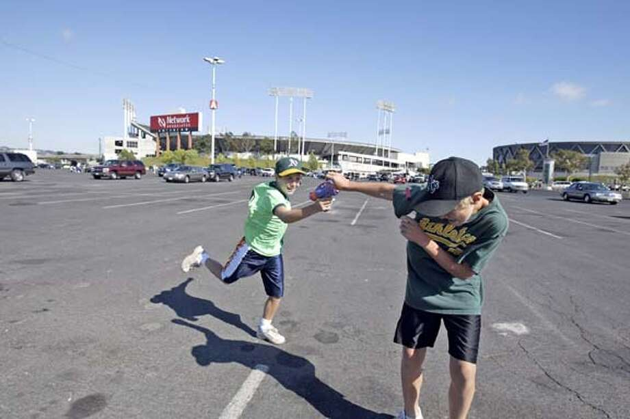 A's fans Troy Carslon, 10, left, and his brother Conrad, 12, play with a toy gun during a tailgate party in the Coliseum parking lot. Chronicle photo by Darryl Bush