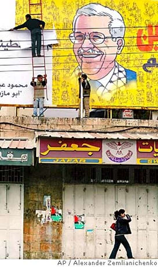 Palestinian youths post a billboard showing President-elect Mahmoud Abbas, also known as Abu Mazen, on top of a building in the West Bank town of Ramallah, Tuesday, Jan. 11, 2005. Abbas, fresh from a landslide victory in an election to replace Yasser Arafat as head of the Palestinian Authority, offered peace talks to Israel just as Israeli Prime Minister Ariel Sharon was installing a new government with a majority for withdrawing from Gaza and part of the West Bank. (AP Photo/Alexander Zemlianichenko) Photo: ALEXANDER ZEMLIANICHENKO