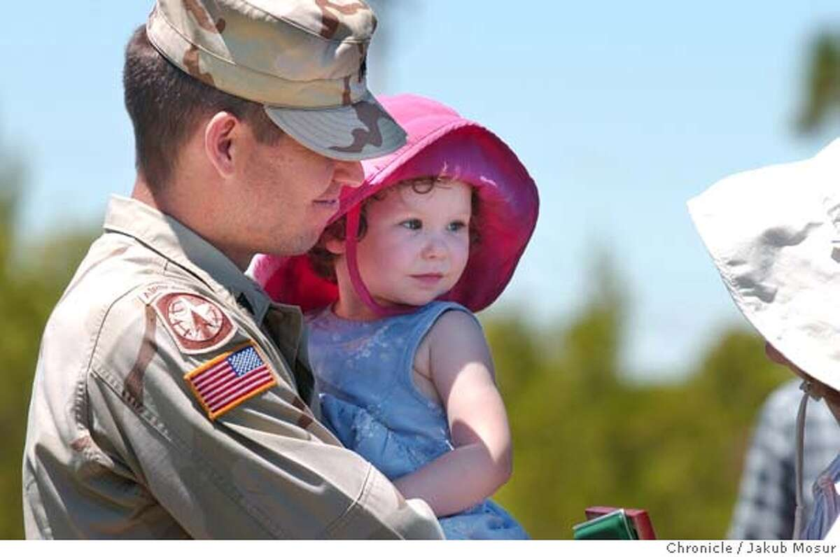 James Crooks, soldier of the 870th Military Police Company of the California Army National Guard, holds his two-year-old daughter, Elizabeth Crooks, after receiving his medal during a welcome home from Iraq ceremony on Saturday,7/24/04 in Pittsburg. The 870th Military Police Company had guarded the Abu Ghraib prison from October of 2003 until April 2004. JAKUB MOSUR / The Chronicle
