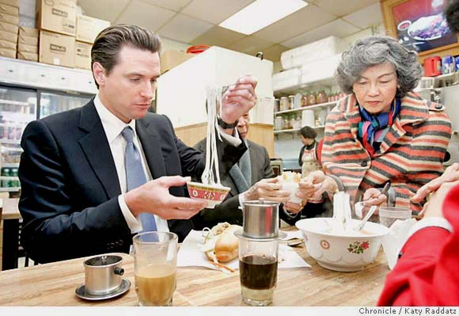 """NEWSOM11271_RAD.JPG SHOWN: Mayor Gavin Newsom eats noodles in broth """"for longevity"""" at the Little Paris restaurant on Stockton Street in Chinatown. The lady serving food on the RIGHT is activist Ann Yuey. Mayor Gavin Newsom hosts a town hall meeting at the Sunset Recreation Center, then goes to Chinatown to meet with the Chinese Six Companies and walk the streets. Photo taken on 1/10/05, in San Francisco, CA.  By Katy Raddatz / The San Francisco Chronicle MANDATORY CREDIT FOR PHOTOG AND SF CHRONICLE/ -MAGS OUT Photo: Katy Raddatz"""