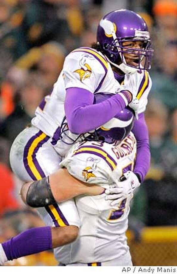 Minnesota Vikings receiver Randy Moss jumps into the arms of tackle Adam Goldberg after catching a 20-yard touchdown pass in the first quarter of their NFC wild-card game against the Green Bay Packers Sunday, Jan. 9, 2005, in Green Bay, Wis. (AP Photo/Andy Manis) Photo: ANDY MANIS