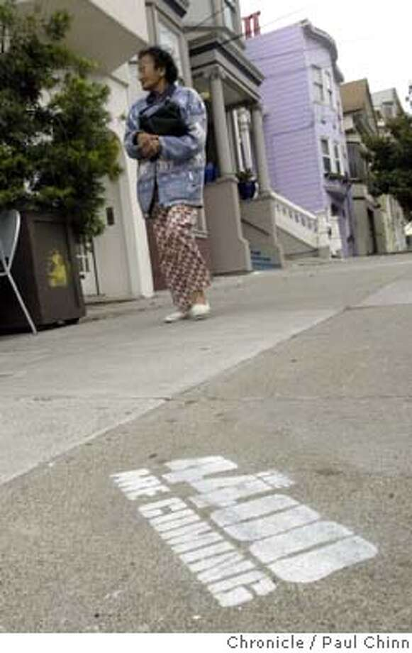 graffiti24_023_pc.jpg A pedestrian walks near an advertisement spray-painted on the sidewalk promoting a new science fiction TV series. The city is demanding the network reimburse the costs for removing the ads. Sidewalk graffiti advertising a cable TV series at 24th and Noe in San Francisco on 7/23/04. PAUL CHINN/The Chronicle MANDATORY CREDIT FOR PHOTOG AND S.F. CHRONICLE/ - MAGS OUT Photo: PAUL CHINN