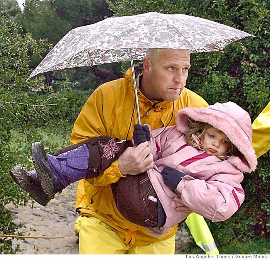 Firefighter Edward Johnson carries Madison Ramirez, 4, whose family was evacuated from The Polynesian Deluxe Mobile House Park in Santa Clarita due to flooding Sunday morning, January 9, 2005. A nearby creek had overflowed into the mobile park.***MANDATORY CREDIT: Genaro Molina/Los Angeles Times MANDATORY CREDIT*** , NO FOREIGN, NO MAGS, LOS ANGELES DAILY NEWS OUT, OC REGISTER OUT, VENTURA COUNTY STAR OUT, INLAND VALLEY DAILY BULLETIN OUT, SAN BERNARDINO SUN OUT Photo: Genaro Molina