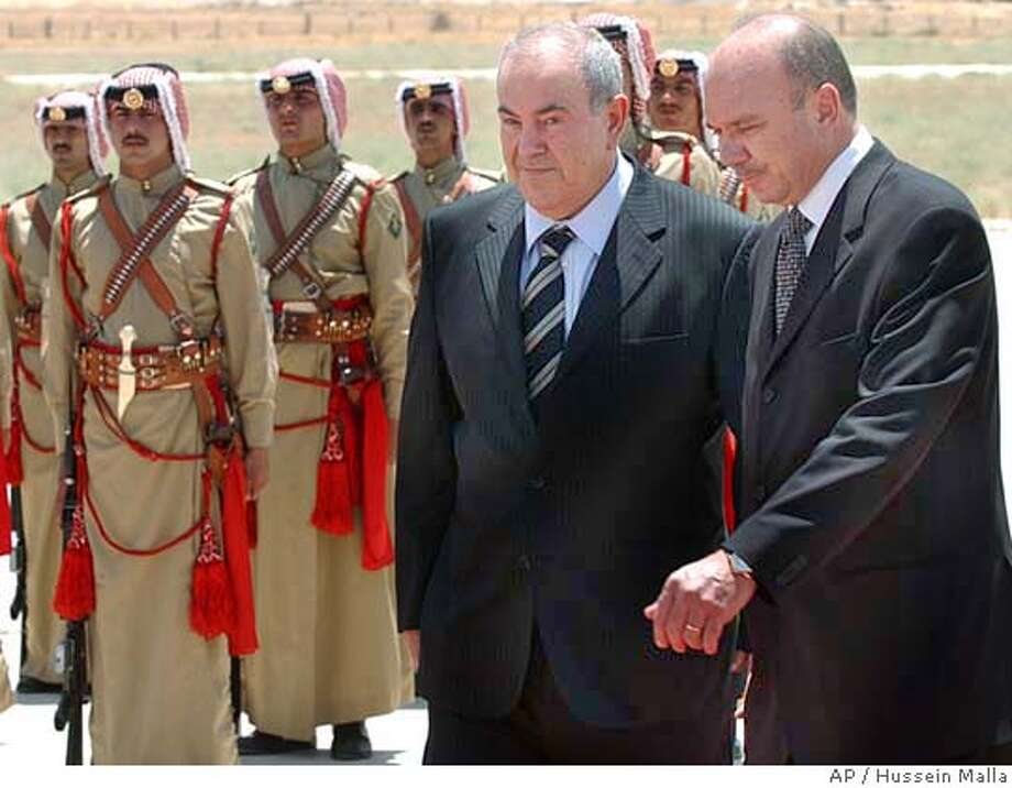Iraqi Prime Minister Ayad Allawi, left center, with his Jordanian counterpart Faisal al-Fayez, right, inspect the Bedouin honor guard upon his arrival at the Marka military air base in Amman, Jordan, Monday July 19, 2004. Allawi began his first regional tour since taking office, arriving Monday in Jordan for talks on postwar reconstruction and resuming cooperation with a neighbor that once was Iraq's largest trade partner. (AP Photo/Hussein Malla) Photo: HUSSEIN MALLA