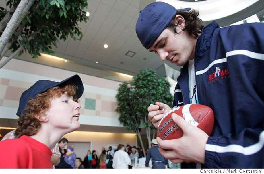 Patient Kelly James gets an autograph from Cal tight end Garrett Cross.  East-West Shrine Game football players visit patients at Shriners Hospital. Mark Costantini / The Chronicle Photo: Mark Costantini