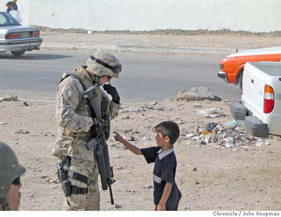 359 -- A Marine on the security detachment talks to an Iraqi boy who wants candy, while the battalion commander talks to the local electricity provider.  Chronicle photo by John Koopman