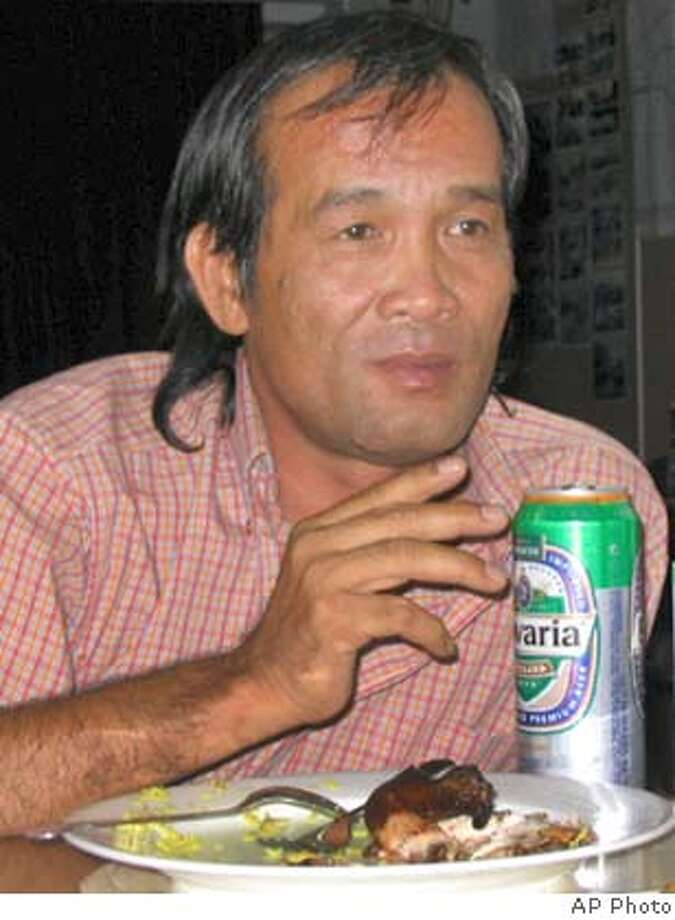 Filipino Driver Angelo de la Cruz, who had been held hostage in Iraq,enjoys a beer and a traditional Iraqi chicken dish at the Philipine embassy after he was handed over to the United Arab Emirates embassy in Baghdad, Iraq, Tuesday July 20, 2004. The hostage drama that has gripped the Philippines for two weeks came to a happy ending Tuesday when insurgents in Iraq freed the Filipino truck driver who has become a national icon at home. (AP Photo) BEST QUALITY AVAILABLE Photo: STR