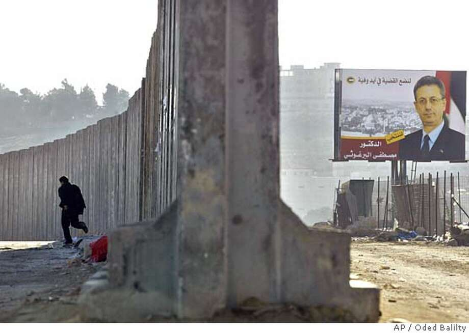 An campaign billboard of presidential candidate Mustafa Barghouti is seen at right as a man walks next to a section of the 8-meter-tall wall, part of the barrier Israel is building to separate the outskirts of Jerusalem from the West Bank, in the village of A-ram outside the West Bank town of Ramallah Saturday Jan. 8, 2005. Palestinians are going to the polls Sunday to elect a successor to the late Yasser Arafat. (AP Photo/Oded Balilty) Photo: ODED BALILTY