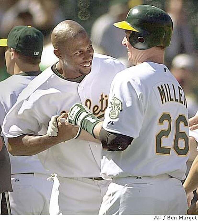Oakland Athletics' Jermaine Dye, left, congratulates teammate Damian Miller (26) after Miller's game-winning bases-loaded single in the 14th inning off Toronto Blue Jays' Justin Speier, not shown, Tuesday, July 20, 2004, in Oakland, Calif. The Athletics won 1-0. (AP Photo/Ben Margot) Photo: BEN MARGOT