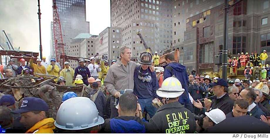 President Bush is surrounded by fire fighters while standing in front of the World Trade Center during a tour of the devastation, Friday, September 14, 2001. Bush is standing on a burned fire truck. Mayor Giuliani said 4,763 people had been reported missing in the devastation of the World Trade Center. (AP Photo/Doug Mills) CAT Ran on: 07-19-2004  President Bush joins firefighters and rescue workers on Sept. 14, 2001, near the site where the World Trade Center stood in New York City. Photo: DOUG MILLS