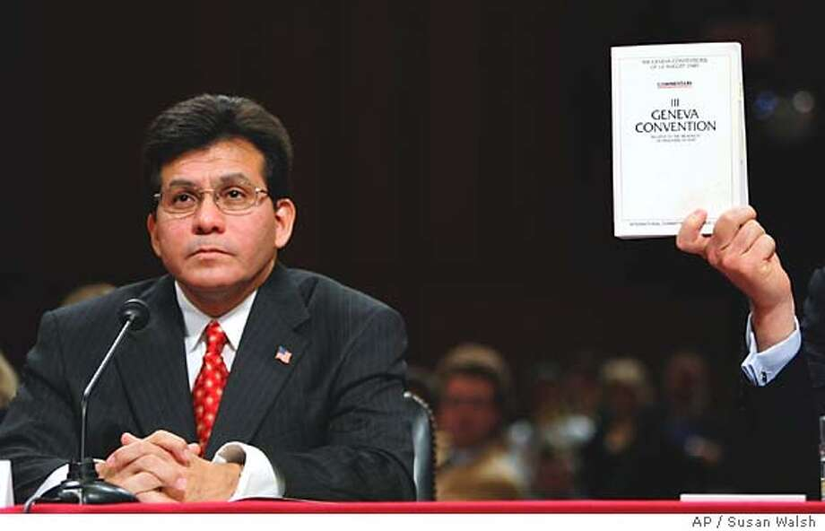Attorney general nominee Alberto Gonzales sits as Sen. John Cornyn, R-Texas, holds up a copy of the Geneva Convention during his confirmation hearing on Capitol Hill, Thursday, Jan. 6, 2004. Gonzales vowed to abide by international treaties on prisoner treatment if confirmed, but Senate critics asserted that policies he supported led to the torture of terrorism detainees and protested his closeness to President Bush. (AP Photo/Susan Walsh) Photo: SUSAN WALSH