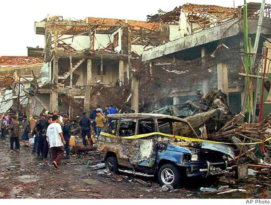 Police officers inspect the ruins of a nightclub destroyed by an explosion in Denpasar, Bali, Indonesia, Sunday, Oct. 13, 2002. Two bomb blasts, one of them exploded about 100 meters (300 feet) from the U.S. consular office, destroyed a nightclub on the tourist island, killing at least 58 people and injuring nearly 180 others, police and hospital workers said. (AP Photo/str) Ran on: 07-18-2004 Photo: STR