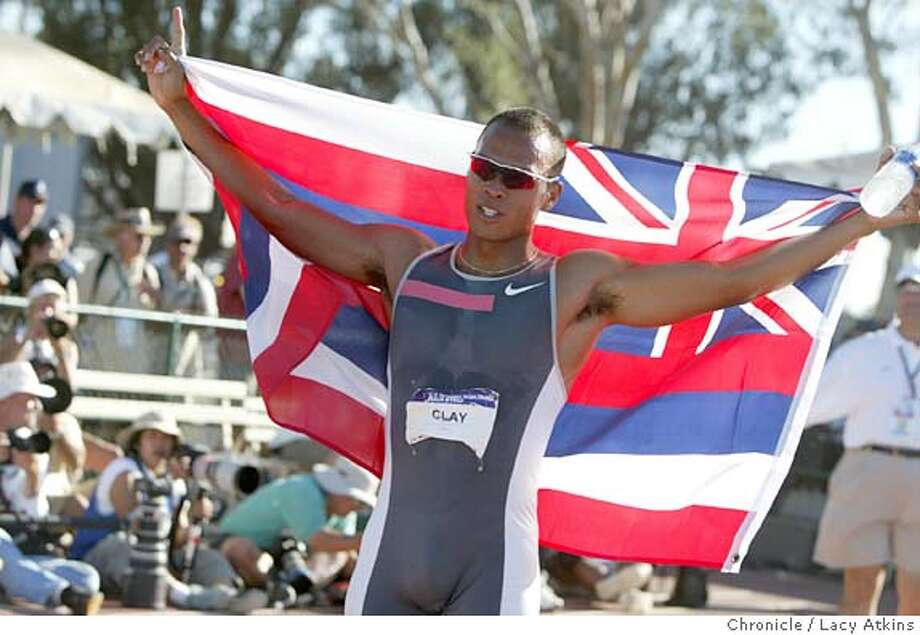 Bryan Clay draped in an Hawain flag at the finish line after winning the Decathlon Finals in the U.S. Olympic Team Trials in Sacramento, July 17, 2004. LACY ATKINS / The Chronicle Photo: LACY ATKINS
