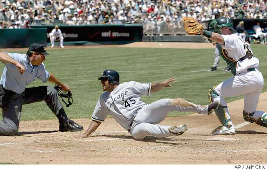 Chicago White Sox's Carlos Lee, center, is called out at home by umpire Angel Hernandez after being tagged out by Oakland Athletics catcher Damian Miller, right, in the second inning in Oakland, Calif. on Sunday, July 18, 2004. The Athletics won 5-3. (AP Photo/Jeff Chiu) Photo: JEFF CHIU
