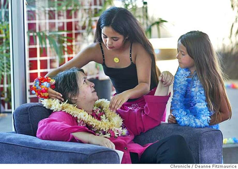 Single mom, Kitty Sanford, who is dying of cancer has a fundraiser at the Children's Discovery Museum to raise money for her daughter, Kuuleilani, 10, (who is putting a lei on her mother) for after she is gone. Friend, Amber Fernandez, 6, looks on. This was shot in San Jose.  Deanne Fitzmaurice / The Chronicle Photo: Deanne Fitzmaurice