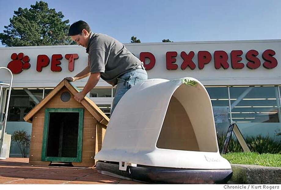 Rosey Mejia of Pet Food Express at Stones Town takes out dog houses and puts them in front of the store. They are going to have a 20 percent sale on dog houses that will last through the end of the month. The San Francisco board of supervisors set new living standards for dogs.  DOGRIGHTS07_0092_kr.JPG 1/6/05 in San Francisco,CA.  KURT ROGERS/THE CHRONICLE MANDATORY CREDIT FOR PHOTOG AND SF CHRONICLE/ -MAGS OUT Photo: KURT ROGERS