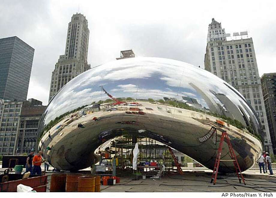 """**ADVANCE FOR MONDAY, JULY 12 ** Workers put finishing touches on the sculpture christened """"Cloud Gate"""" July 7, 2004, at Chicago's Millennium Park. The sculpture of polished steel plates is part of the $475 million project between Lake Michigan and bustling Michigan Avenue to be opened to the public July 16. (AP Photo/Nam Y. Huh) HFR 07-15-04. ADVANCE FOR WEEKEND JULY 15-18 Photo: NAM Y. HUH"""